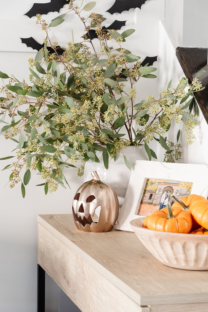 halloween home decor on table gold jack-o-lantern and seeded eucalyptus