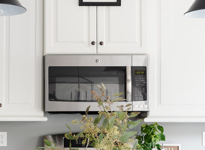 eucalyptus in vase in kitchen and trick or treat sign on cabinet