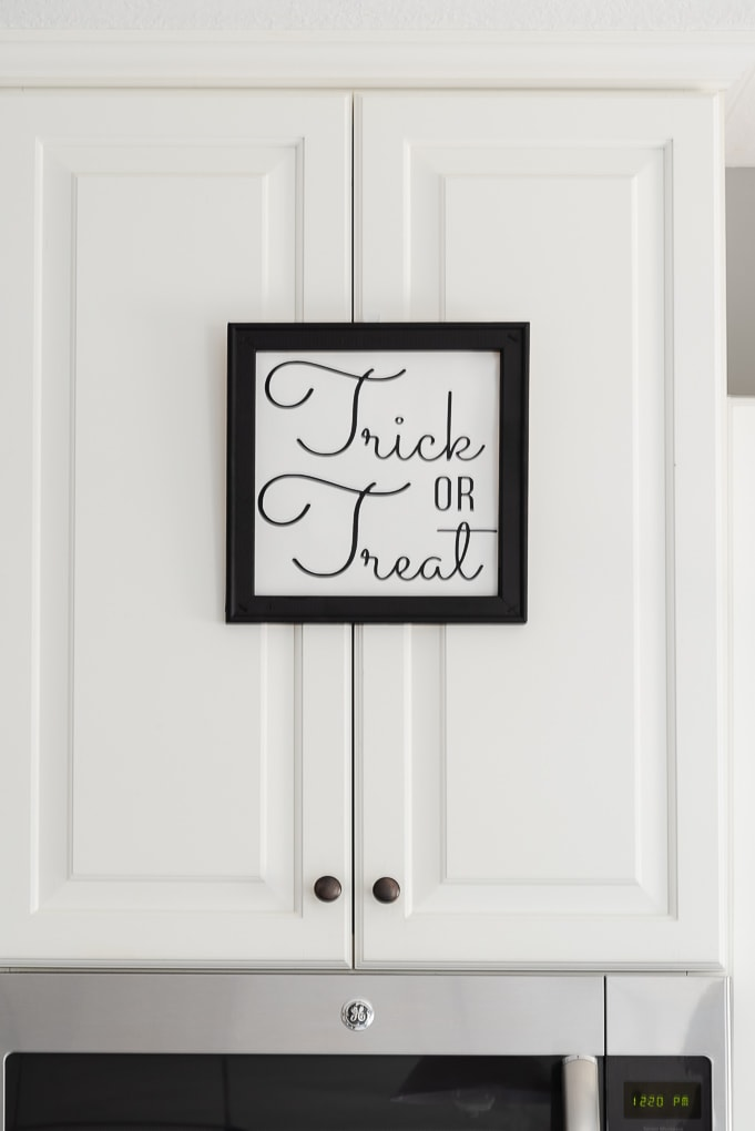black and white trick or treat sign on white kitchen cabinet