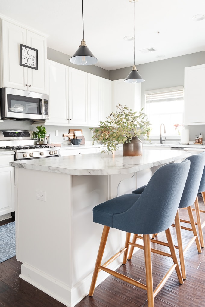 white kitchen with blue counter stools next to island
