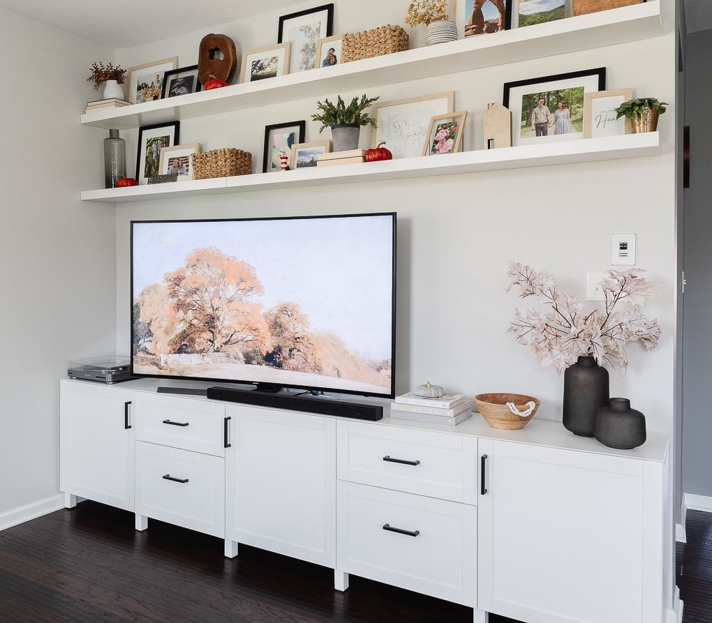 fall tv art with media console and decorated fall floating shelves above
