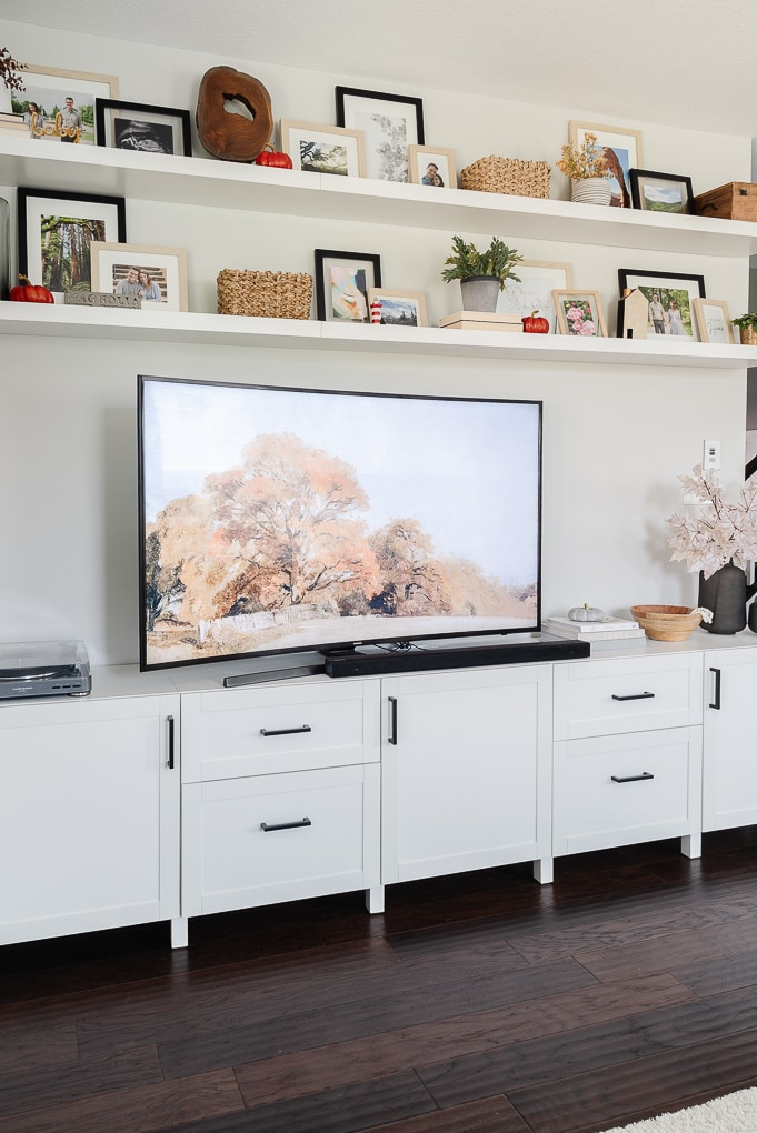 fall tv art with decorated floating shelves above