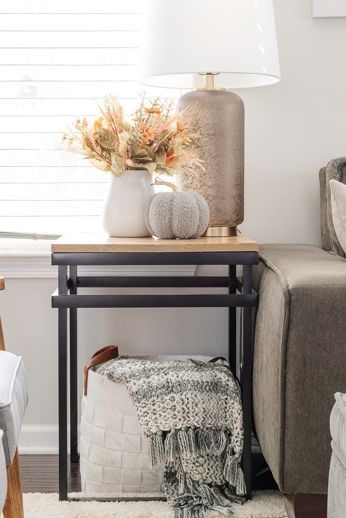 knitted pumpkin and vase of fall florals on end table with throw blanket in a basket