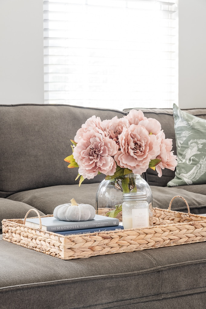 woven tray on ottoman with fall decor and vase with flowers