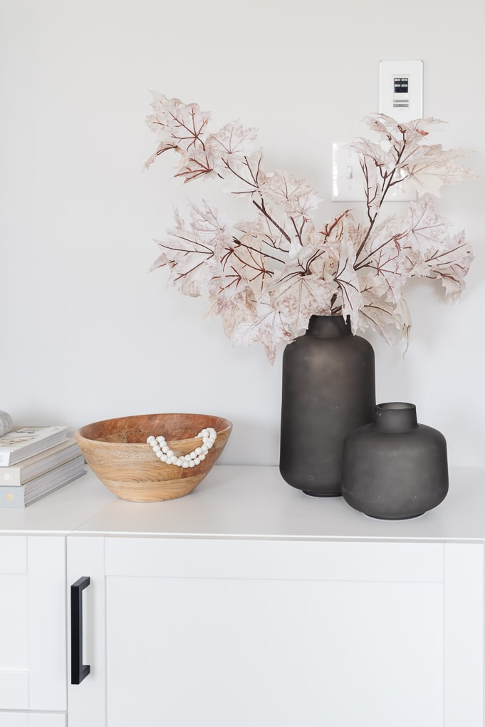 black vases with fall leaves and wooden bowl home decor