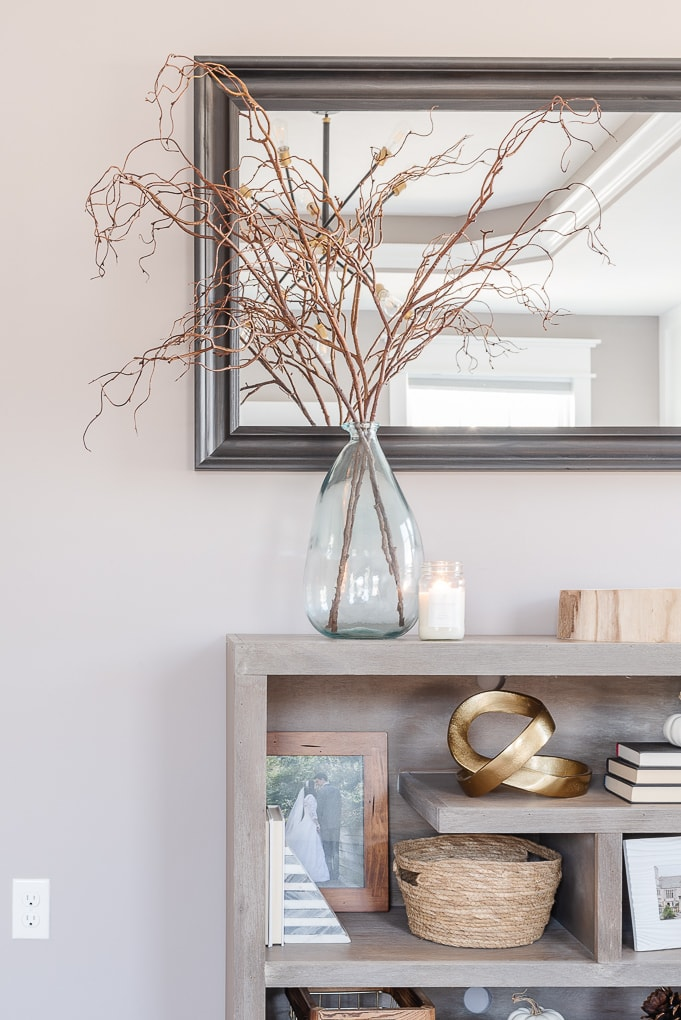 fall candle on bookshelf with decorative vase and branches