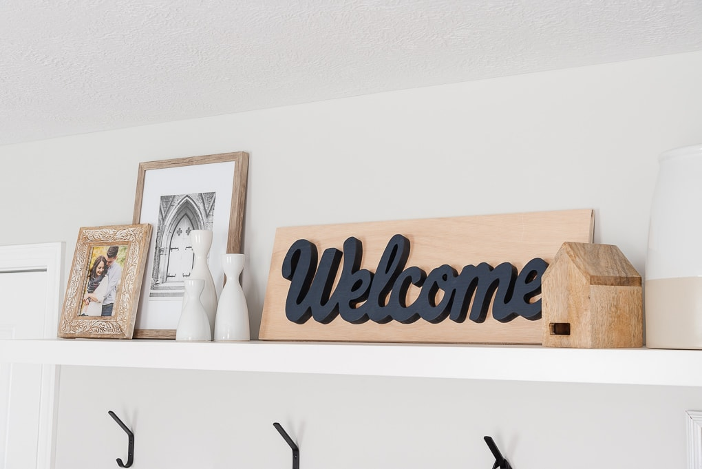 wooden welcome sign and other decor on entryway shelf