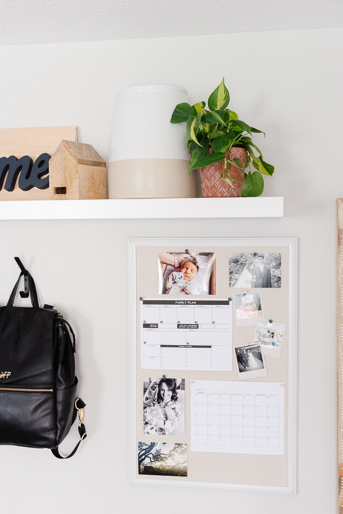 bulletin board with photos and printables and a shelf with a plant