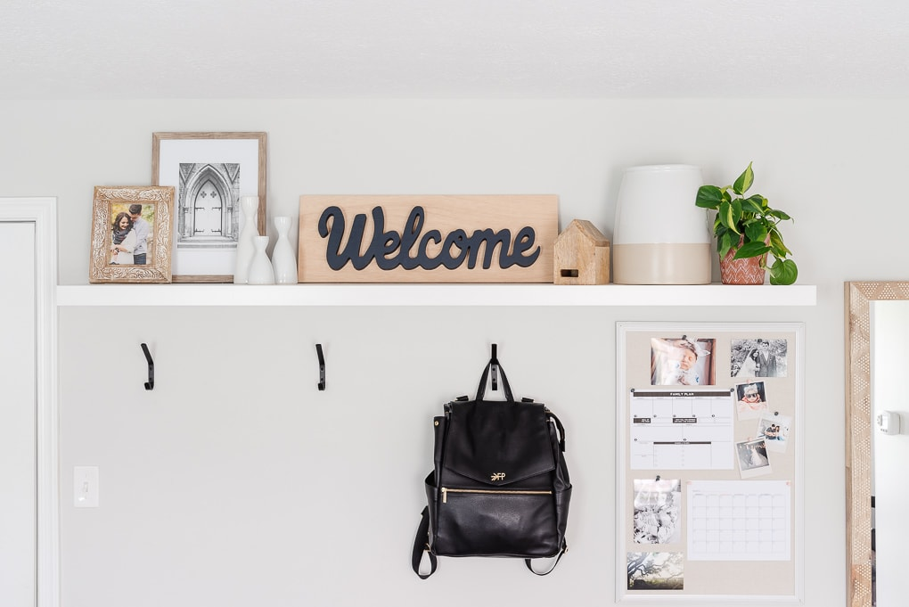 entryway hooks and decorated shelf