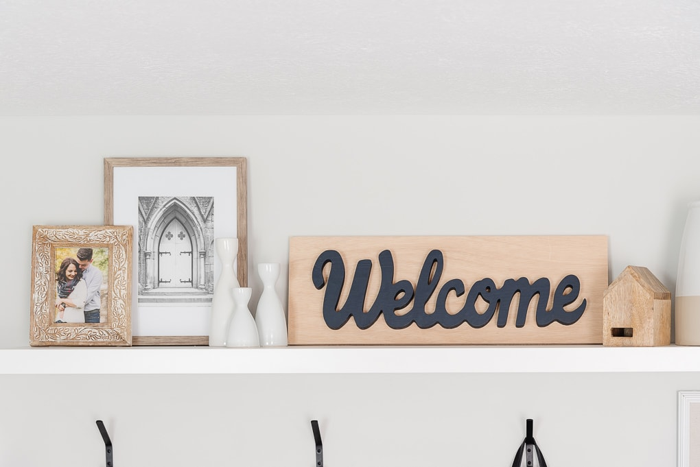 wooden welcome sign in entryway on shelf with other framed decor