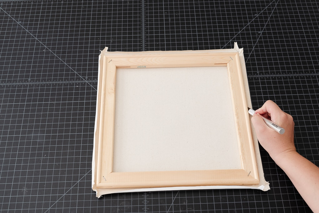 cutting away white canvas to fit behind wooden frame