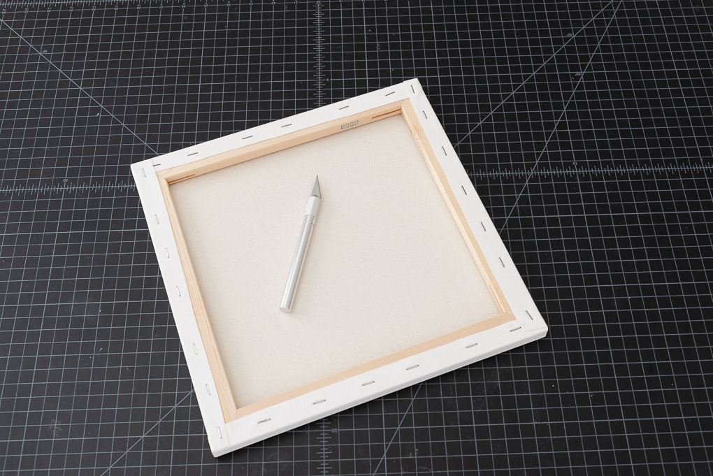 back of white square canvas and exacto knife