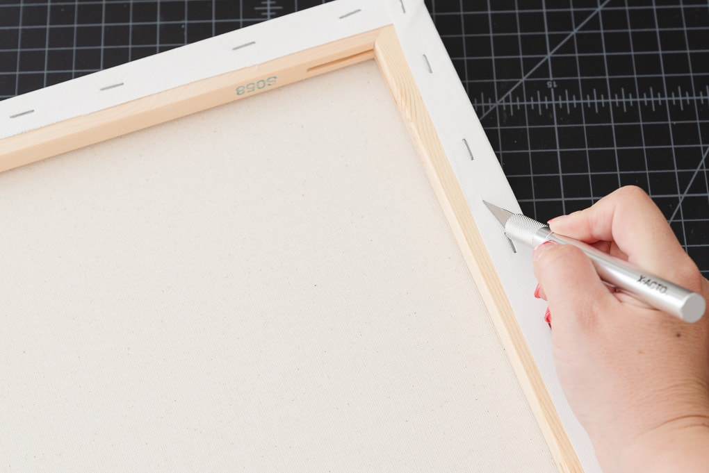 cutting white canvas away with an exacto knife