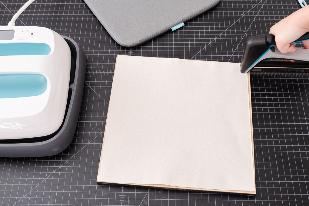 using a staple gun to attach white canvas to a frame