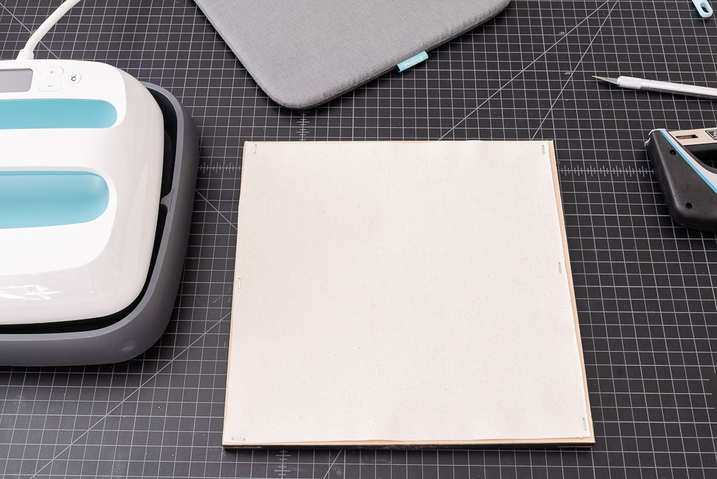 staples attaching a white canvas to a wooden frame