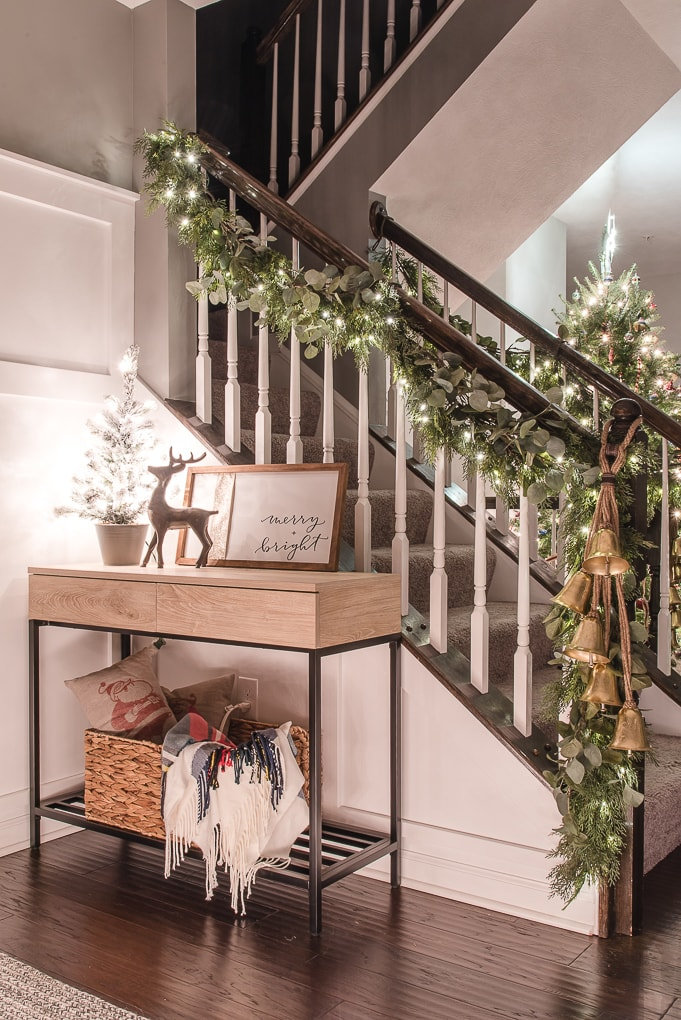 christmas garland at night with twinkle lights and console table with mini tree