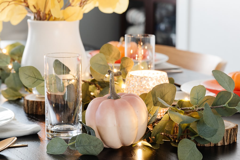 pink ombre pumpkin in faux eucalyptus on thanksgiving table decor