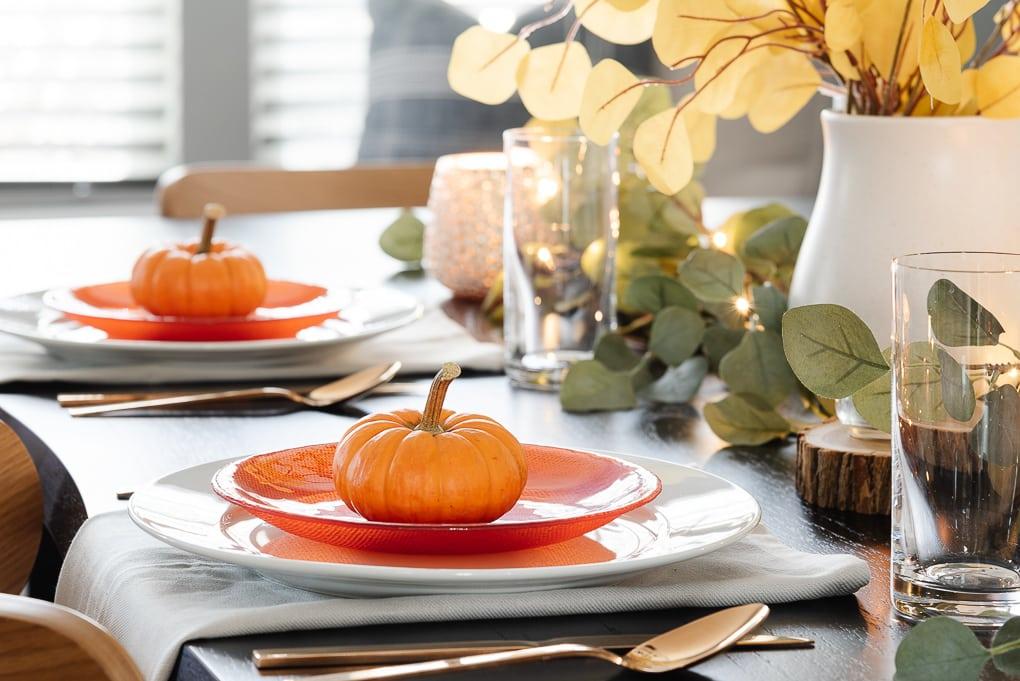 mini pumpkin on dinner plate on thanksgiving table