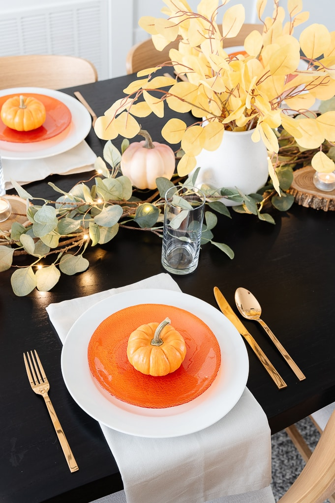thanksgiving table setting white plate and orange salad plate with mini pumpkin on top