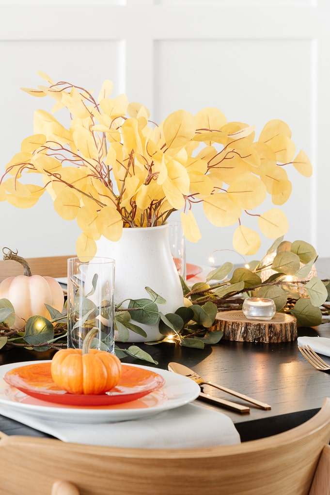 white ceramic vase with yellow eucalyptus stems centerpiece thanksgiving table