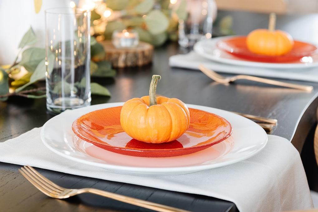 mini orange pumpkin on orange salad plate