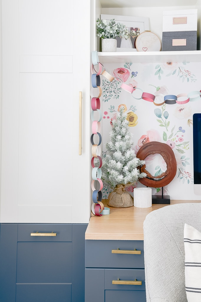 flocked tree on built in desk top with other colorful Christmas decorations