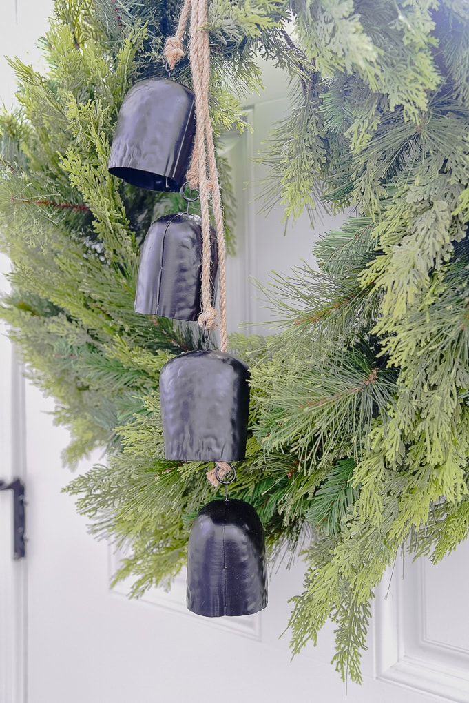 Close up detail of mcgee and co Christmas greenery wreath on door with black bells