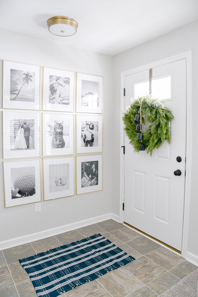 modern gallery wall in entryway with Christmas wreath on the door