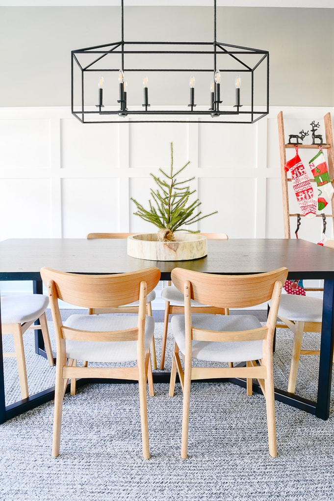 sparse tabletop Christmas tree in natural round wooden tray on top of modern black dining room table