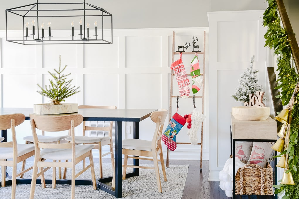 Dining room decorated and styled for Christmas with festive modern decor and staircase greenery garland and stocking ladder