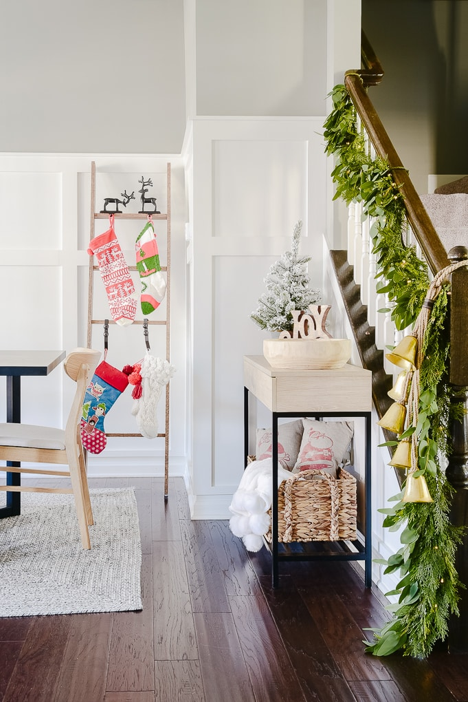 Christmas stocking ladder against white board and batten wall and staircase with Christmas greenery garland