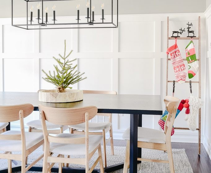 dining room decorated for Christmas with tabletop tree and stocking ladder