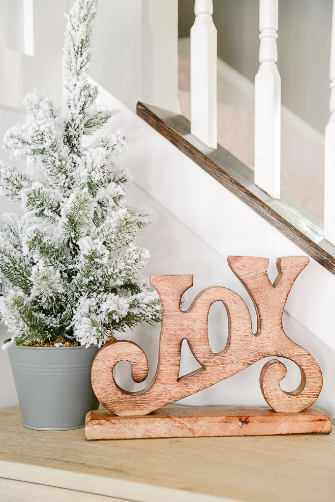 flocked tabletop Christmas tree next to natural wooden Joy figurine