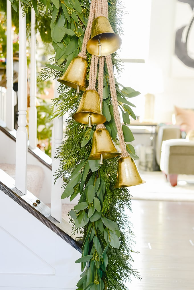gold bells hanging on staircase at the end of Christmas garland