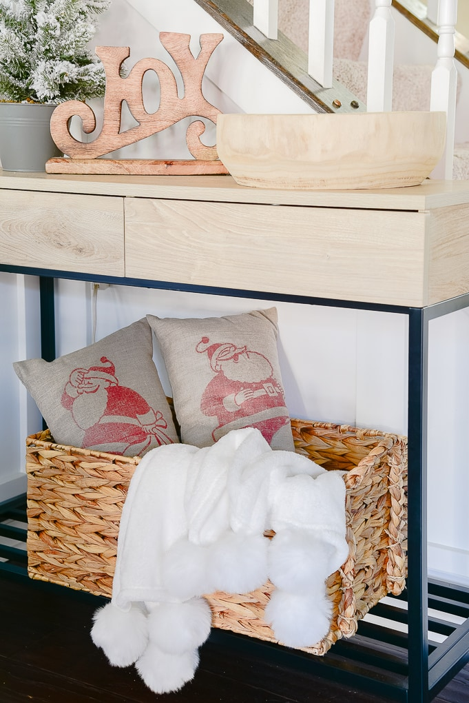 woven basket under console table filled with two Santa pillows and a white pom pom throw blanket