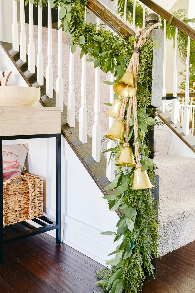 staircase in Christmas dining room with pine and eucalyptus Christmas garland and strand of gold hanging bells