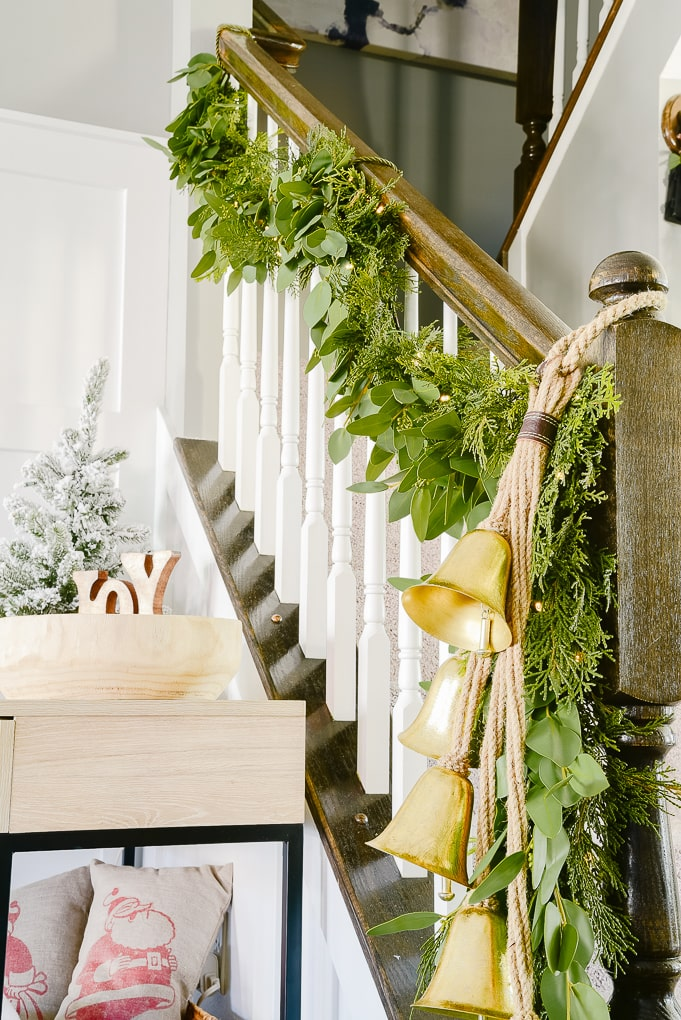 hanging golden Christmas bells attached to pine and eucalyptus Christmas garland on staircase