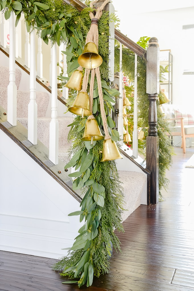 pine and eucalyptus Christmas garland at end of staircase with strand of golden hanging bells