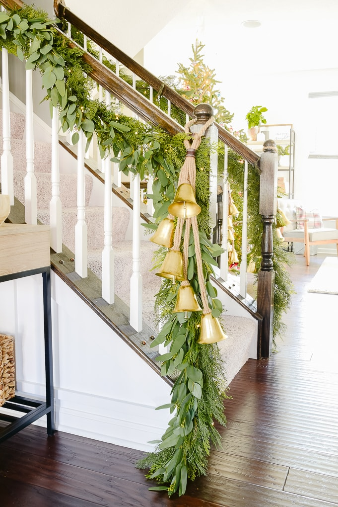staircase with pine and eucalyptus Christmas garland and golden bells