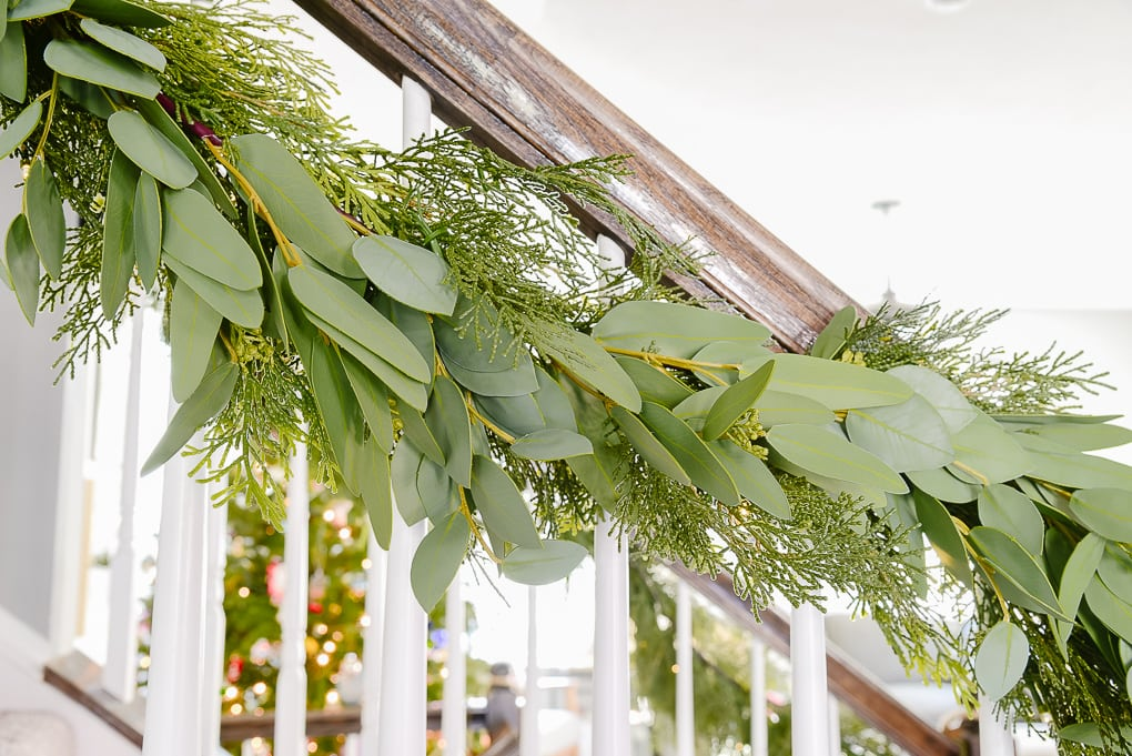 pine and eucalyptus Christmas garland attached to staircase railing