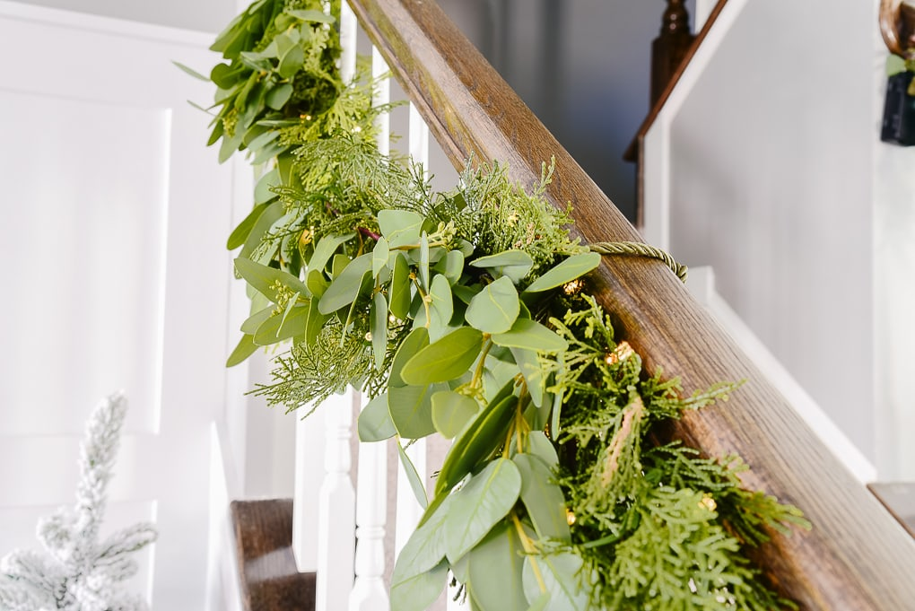 pine and eucalyptus garland attached to staircase railing