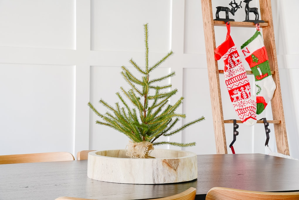 tabletop sparse Christmas tree in wooden round tray in Christmas dining room