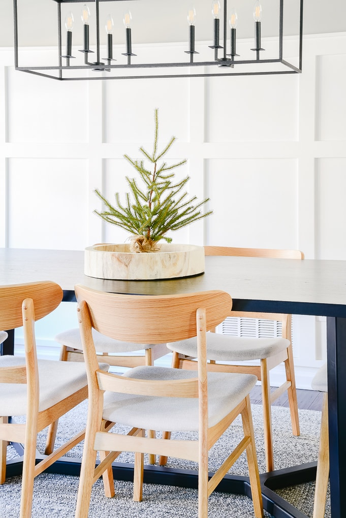 tabletop sparse Christmas tree in wooden round tray on black dining room table
