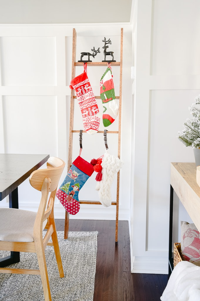 modern classic Christmas stocking ladder with four knitted Christmas stockings hung