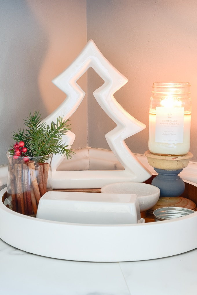 white tree figurine on tray in kitchen next to candle burning