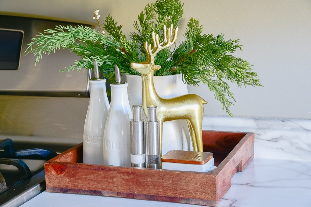 Christmas kitchen decor tray with greenery in a white vase and gold reindeer