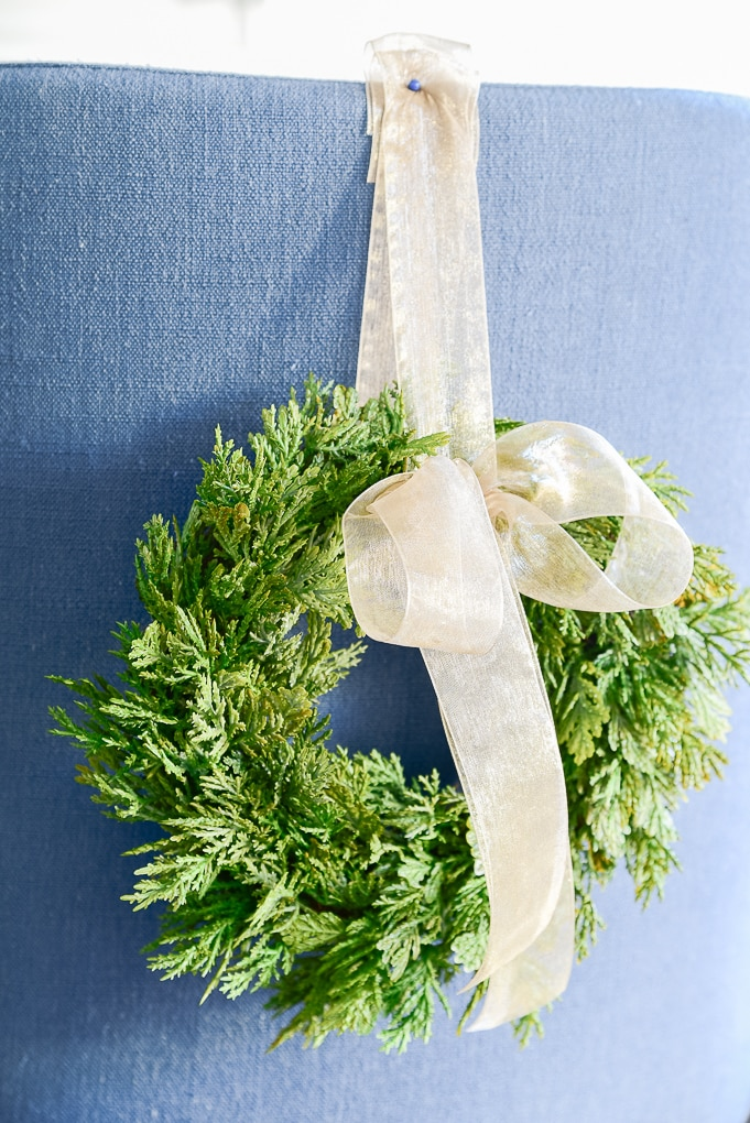 close up of green mini Christmas greenery wreath with bowl attached to blue counter stool