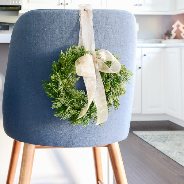 green mini Christmas greenery wreath with bowl attached to blue counter stool