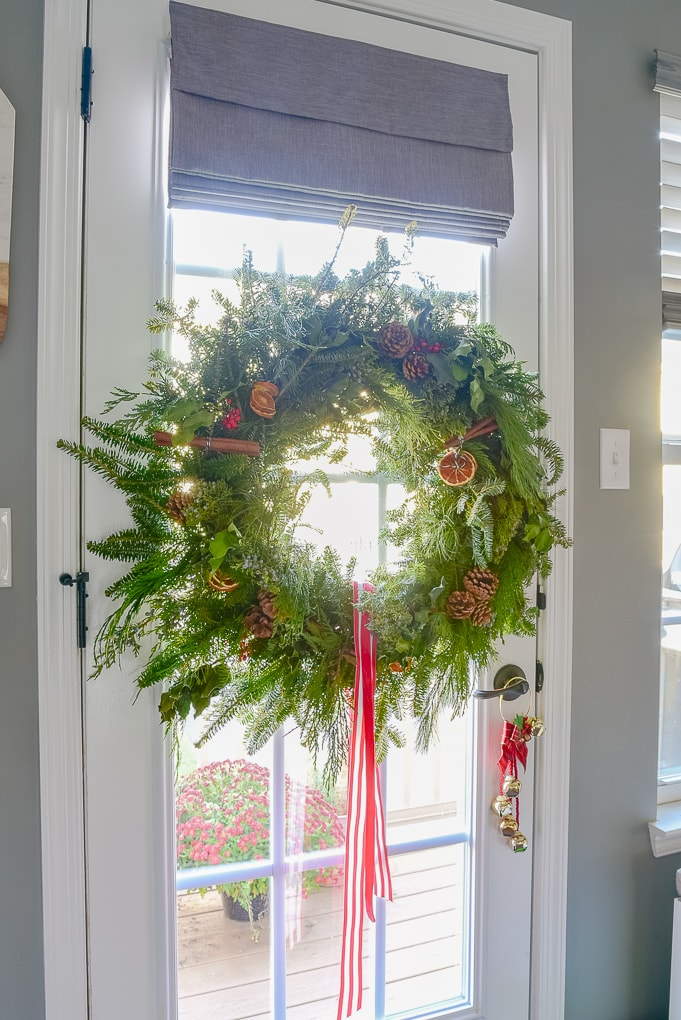handmade fresh Christmas greenery wreath on glass door