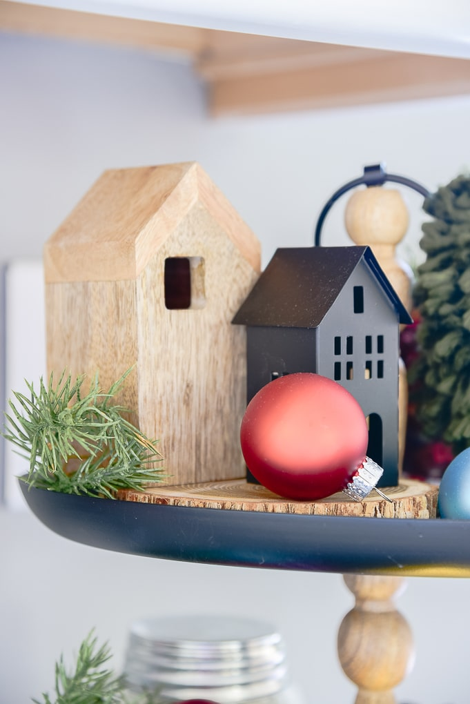 Miniature houses on black metal tiered tray decorated with Christmas ornaments